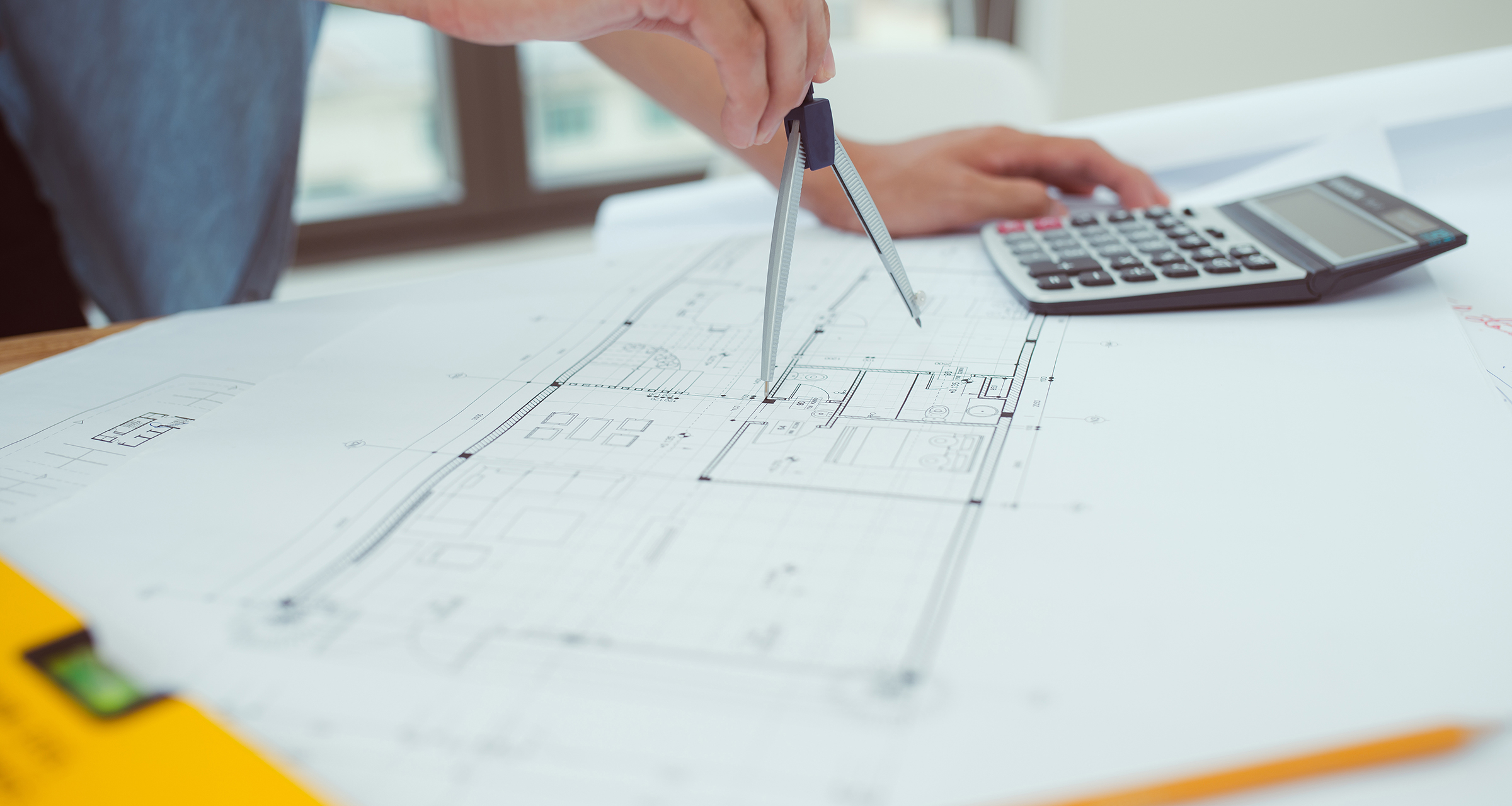 Architect is drawing the plan and calculator is on the table